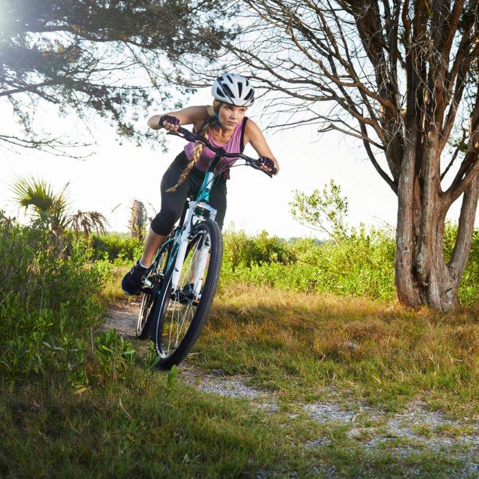 A woman riding a dirt bike on a rugged trail