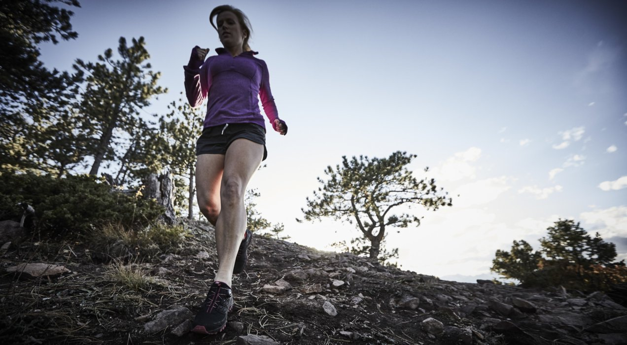 Athlete woman running in the woods down a hill