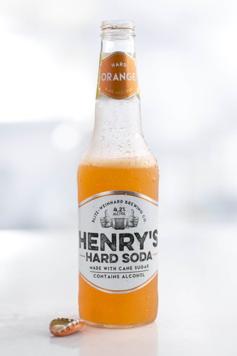 Henry's hard soda orange with the cap on the side