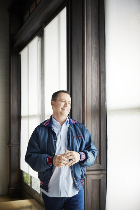 Portrait of a happy man in front of large windows