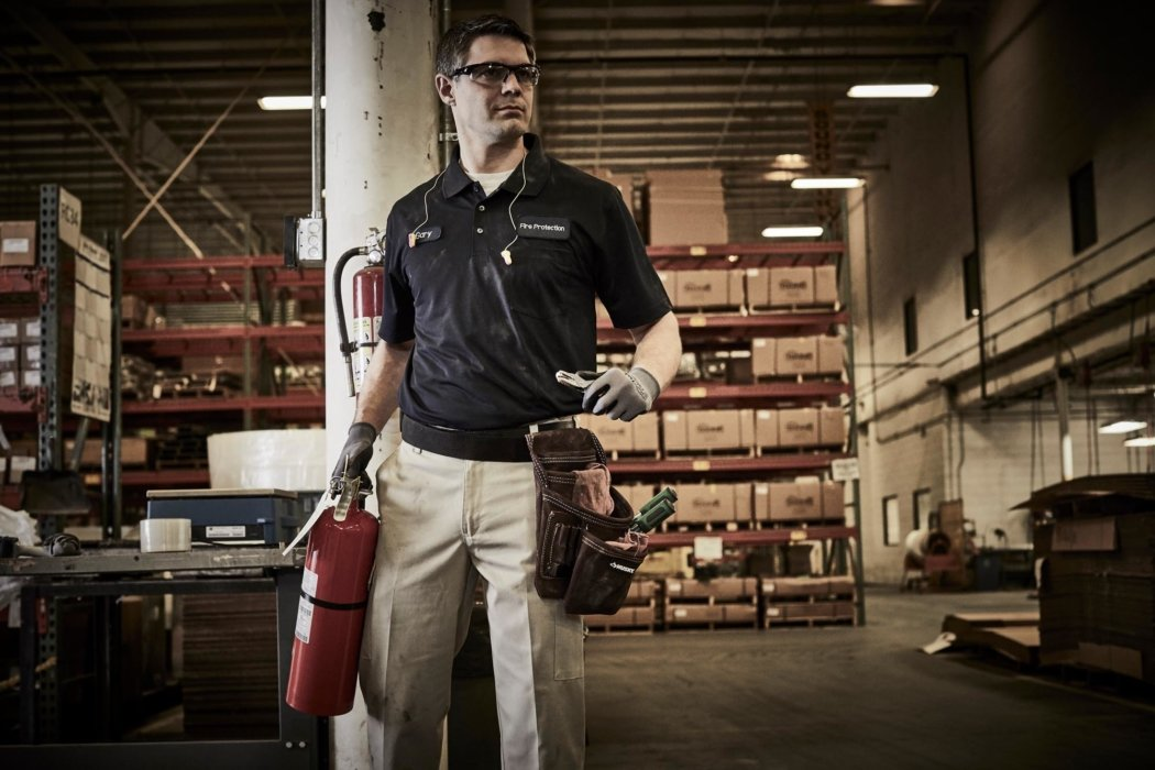 A man working with a fire extinguisher - workplace photography