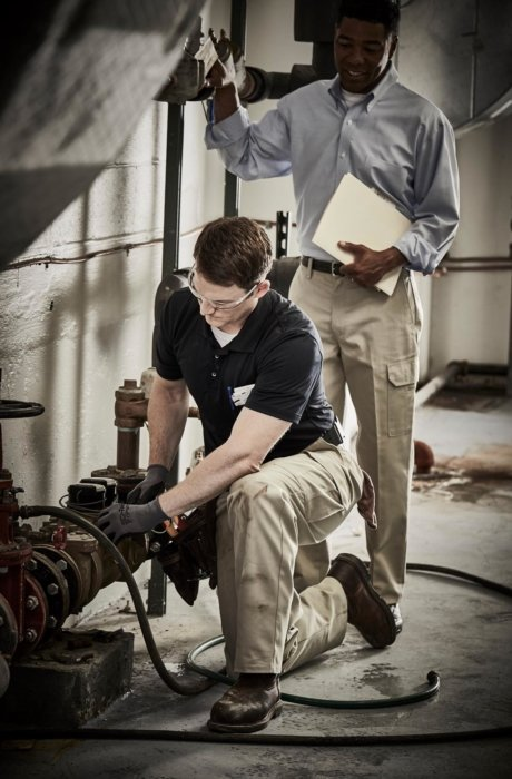 Two men inspecting equipment at a job site - workplace photography