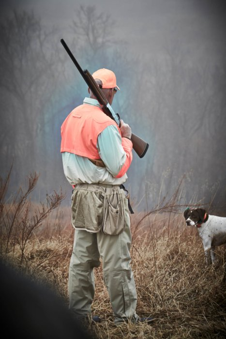 A hunter with shotgun and dog - outdoor hunting photography