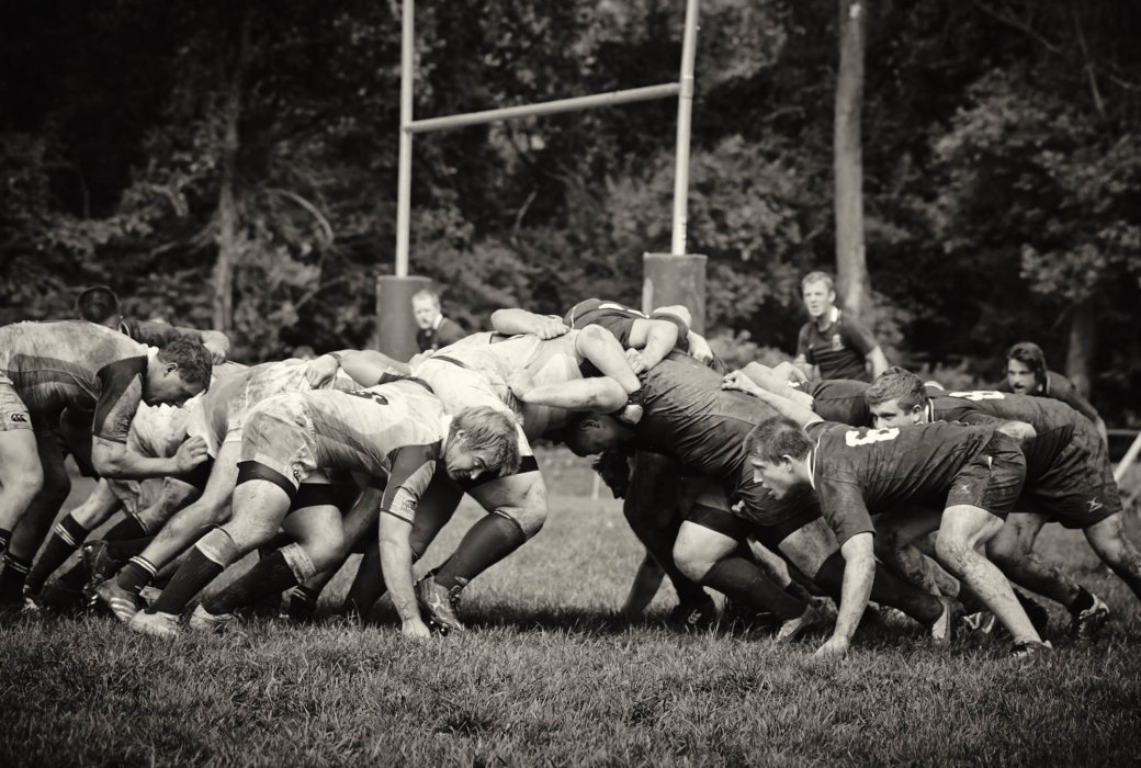 Young athletic rugby players pushing in a play