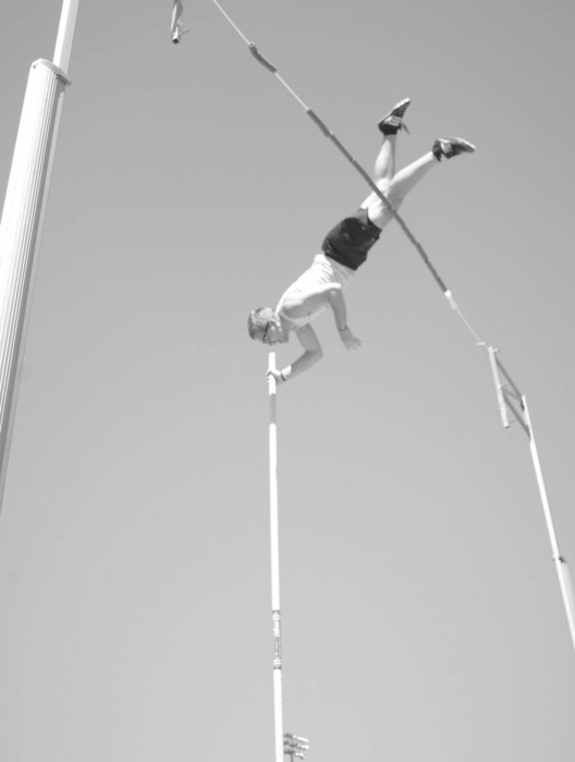 A pole vault athlete in the middle of a jump