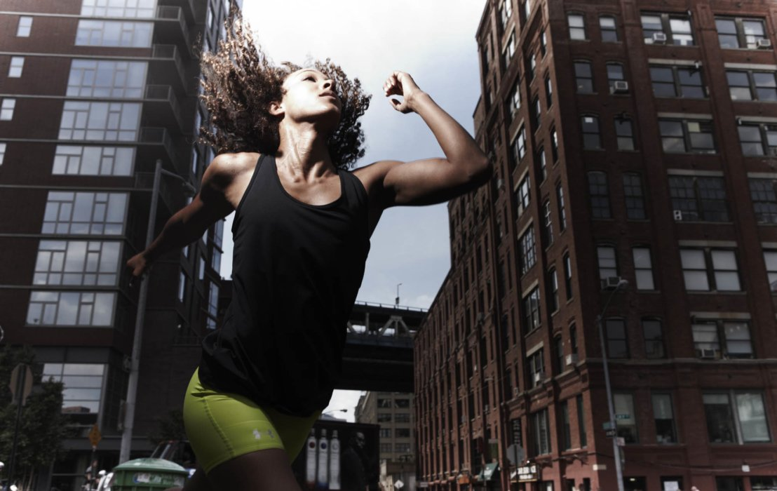A young woman athlete running in a city