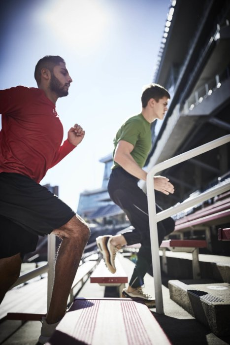 Two male runners going up stadium steps training
