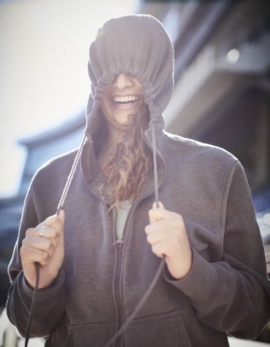 A young woman athlete pulling the drawstring on hoodie - athlete photography