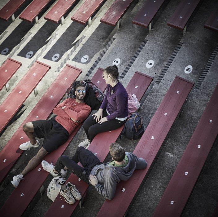 three athletes taking a break from training on stadium steps