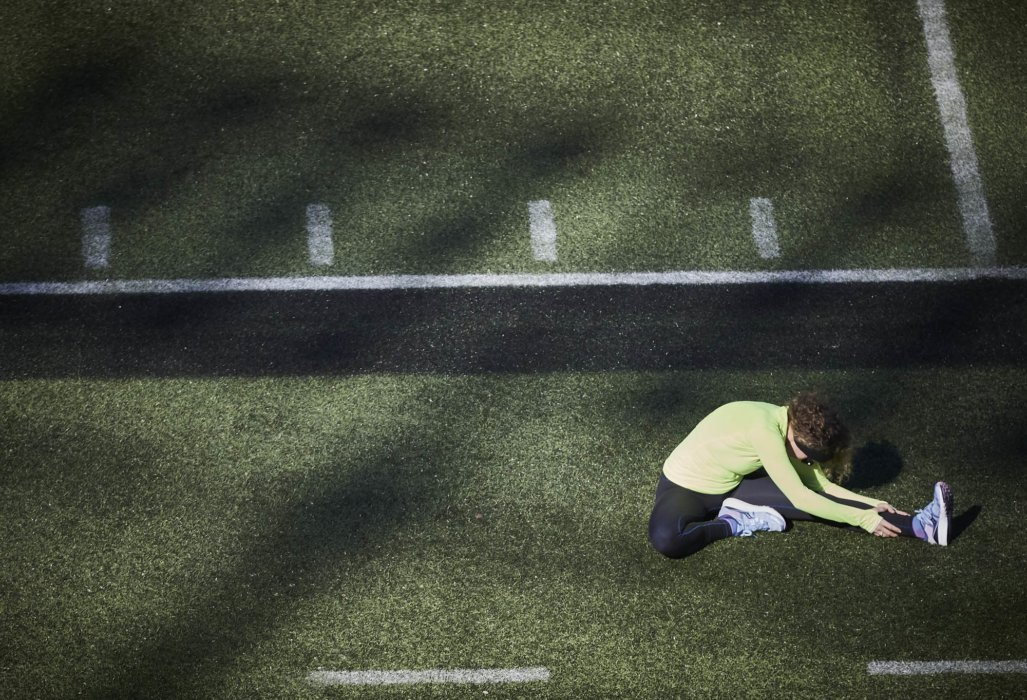 A young female athlete stretching on a field before running