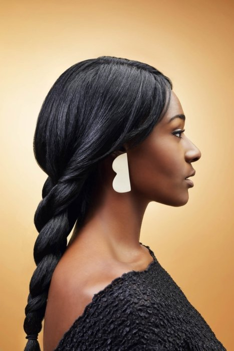 A young woman wearing high-end ceramic ear rings on a golden background