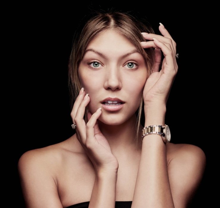 A portrait of a woman wearing a nice watch and rings