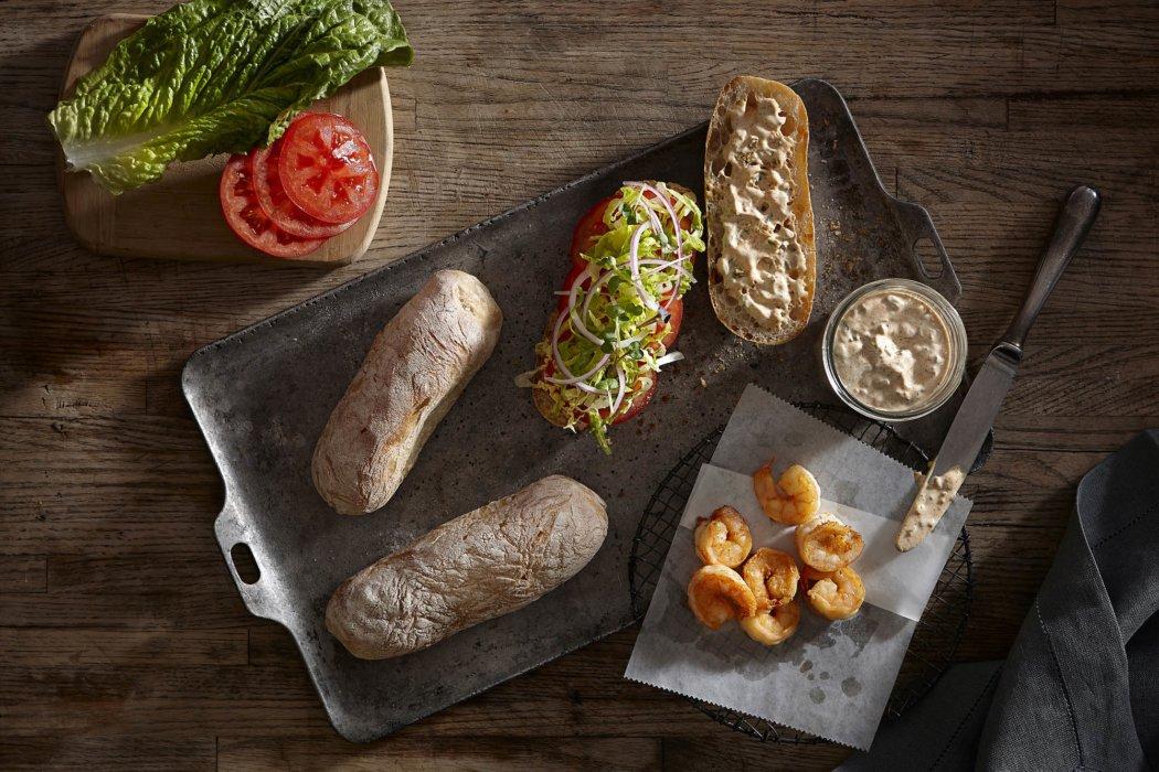 A beautiful po boy sandwich being prepared on a tray