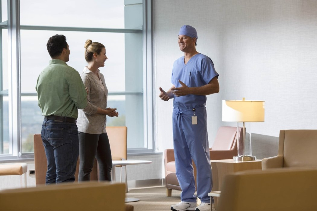 A doctor in scrubs talking to family members in a waiting room   Healthcare Photographer