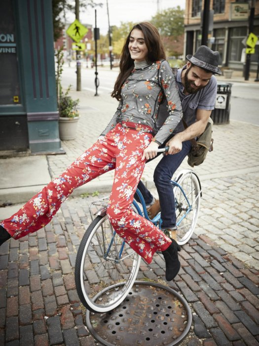 A couple riding a vintage bike on a brick road