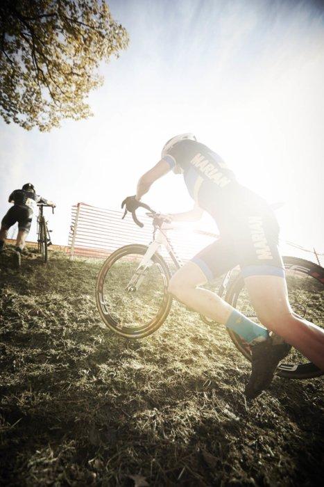 Cyclocross ride in a race pushing his bike
