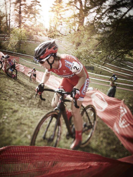 Cyclocross rider riding through mud up a hill