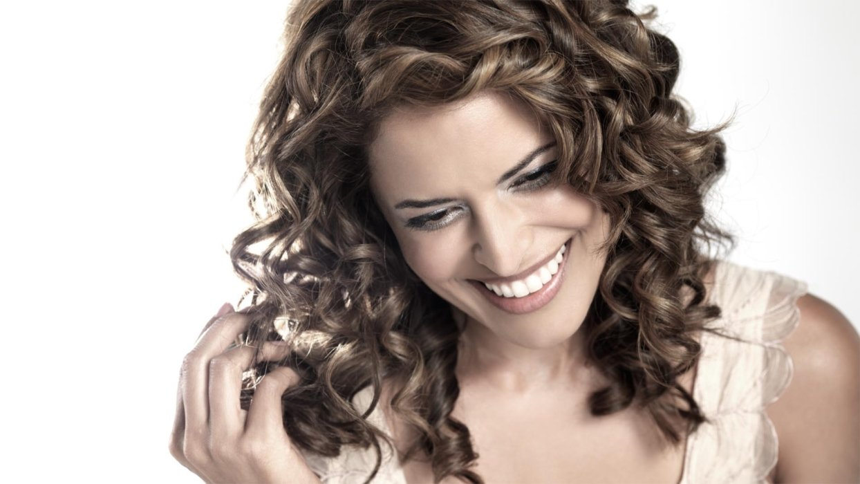 Beauty shot of woman with big curls smiling white touching her hair
