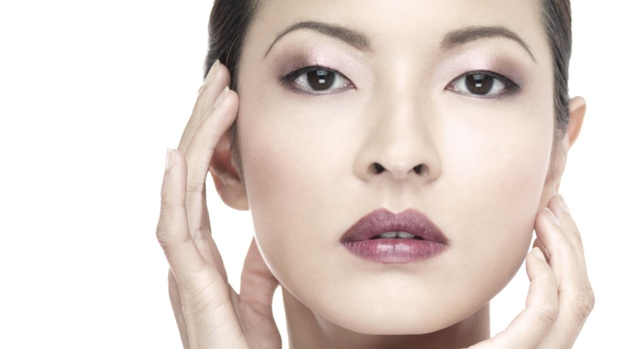 Beauty shot of a woman holding her hands up to the sides of her face