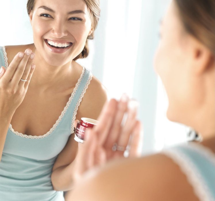 Beauty shot of a young woman applying Olay beauty product