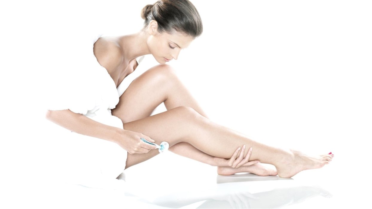 Beauty shot of a woman shaving her legs in a white robe