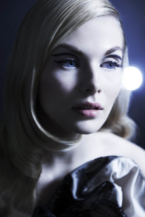 A beauty shot of a blonde woman with thick eyelashes