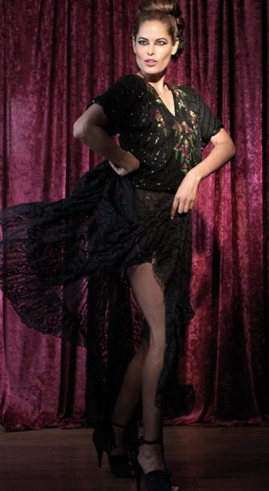 A fashion model wearing a dark dress dress with a vintage style dancing