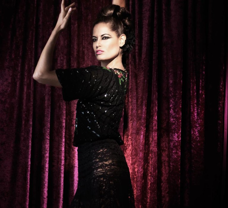 A fashion model wearing a dark dress dress with a vintage style