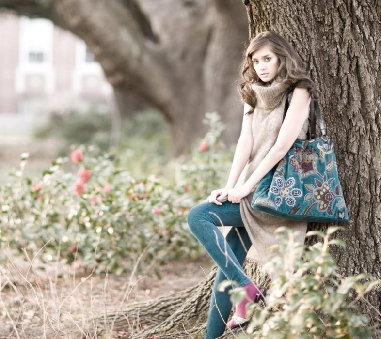 A fashion model leaning against a tree wearing vintage fashion