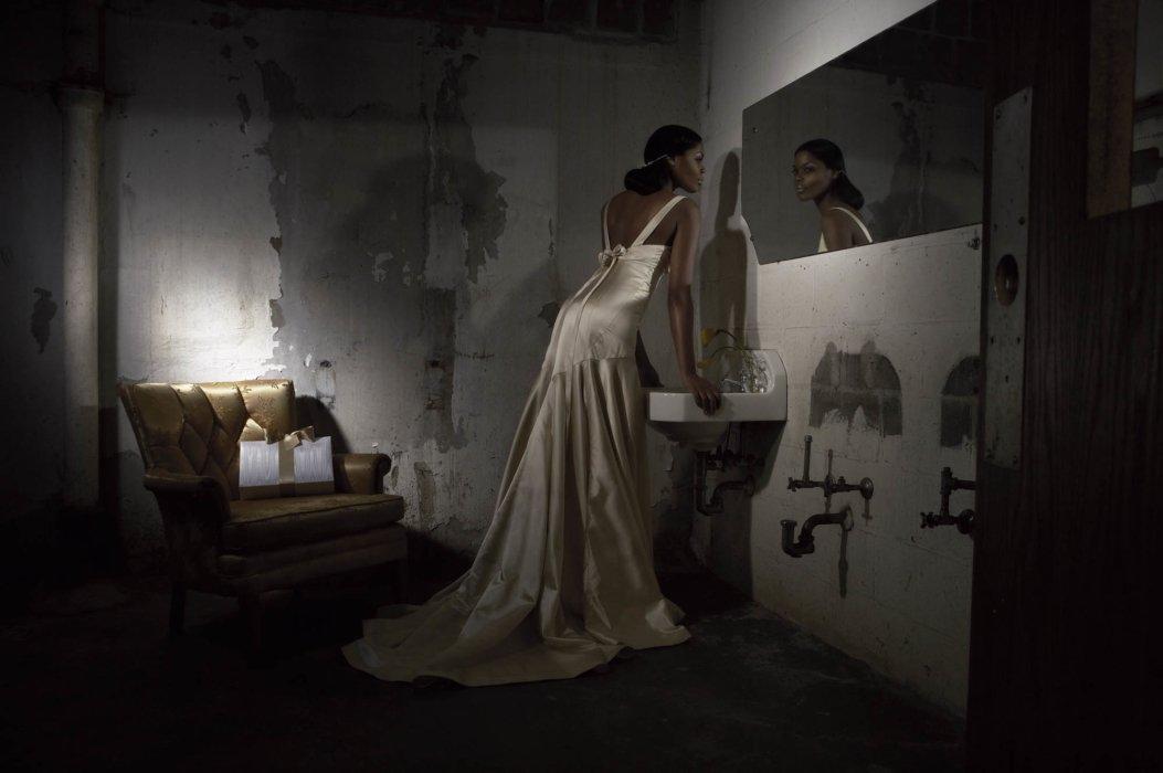 A fashion model wearing a wedding dress in a dark setting