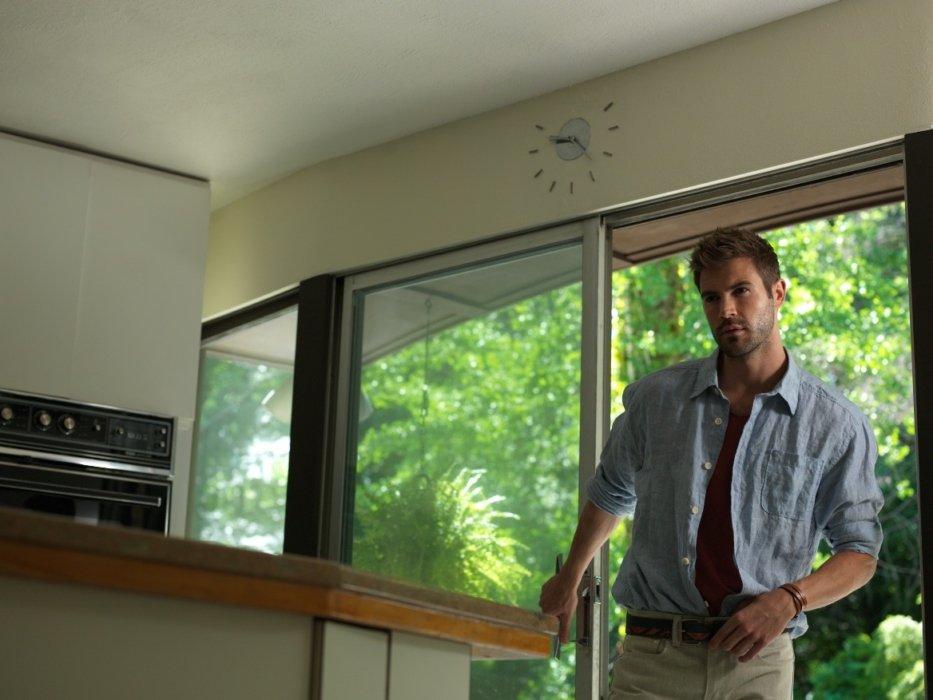 A fashion model male walking through a kitchen