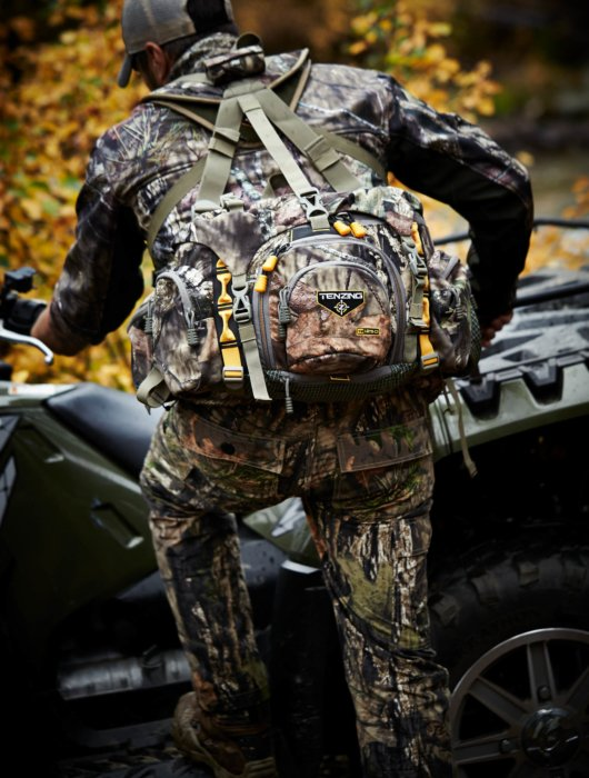 A hunter in tenzing hunter gear getting on an atv