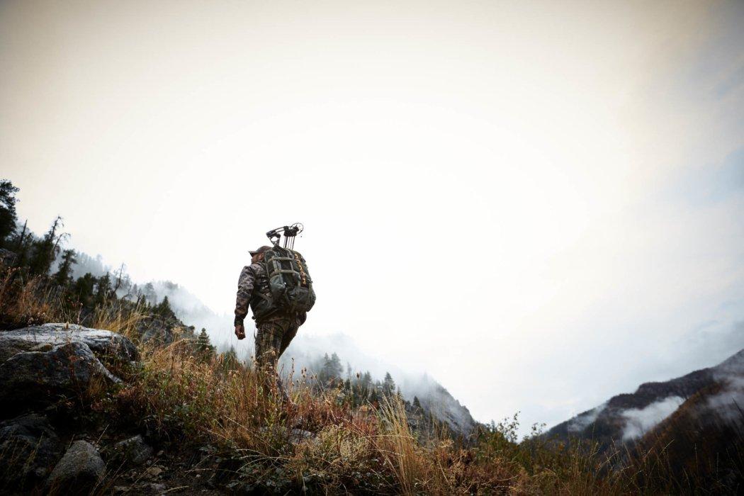 A hunter with tenzing gear climbing up a moutain