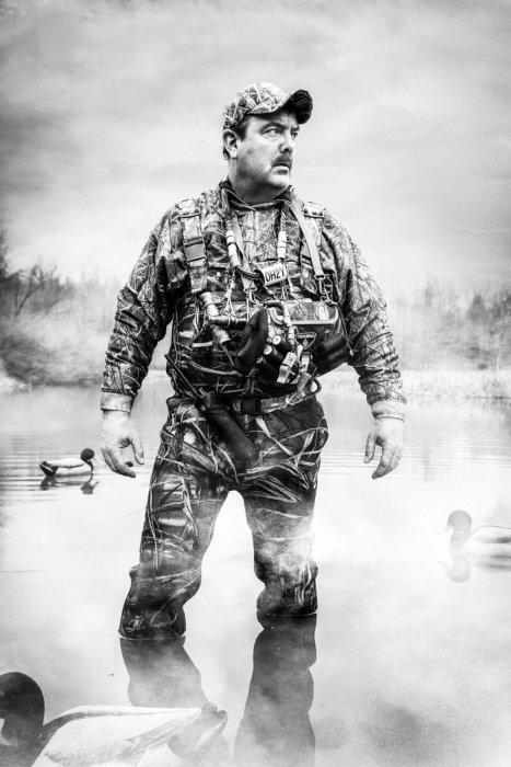 Portrait of a duck hunter wading near decoys