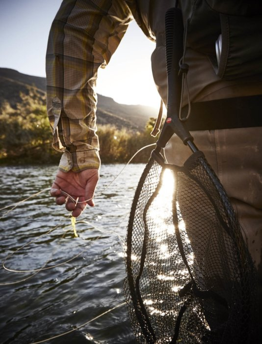 A fly fisherman holding his bait and line in a stream