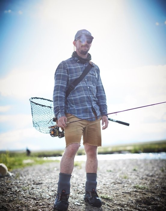 A portrait of a young fisherman with net and rods