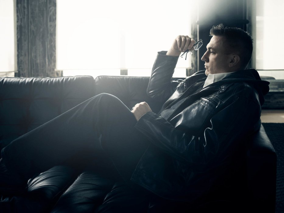 Portrait of man with glasses reclining on a couch