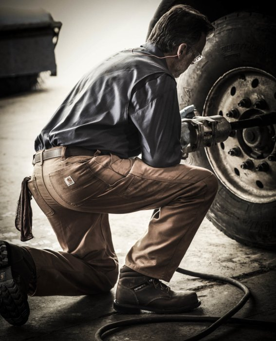 A man working on the wheels of a truck with rugged work apparel
