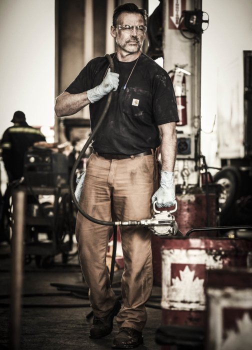 A man in car-hart work apparel in a large mechanic setting