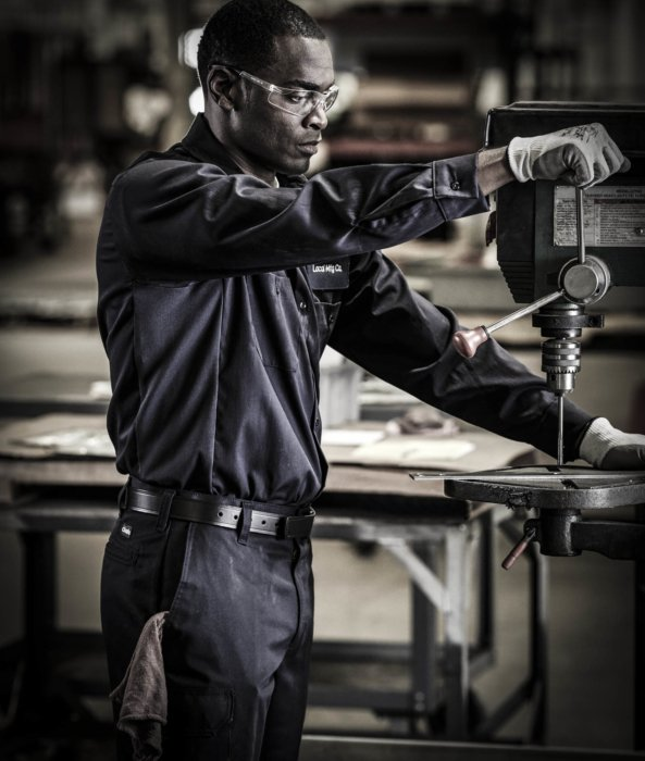 A man working at a drill press with metals