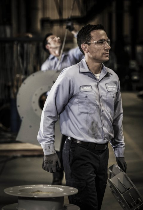A man moving fan parts at an industrial facility
