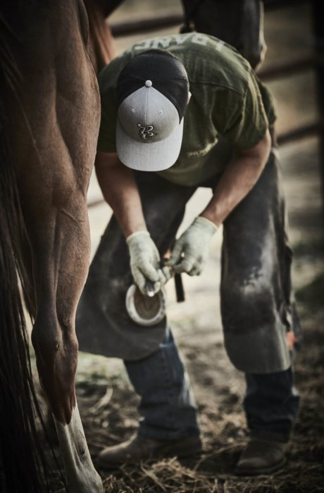 a rancher working on horse shoes