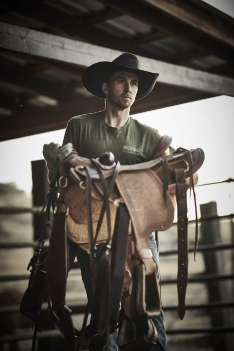 A rancher wearing rural cloth apparel holding his sadle