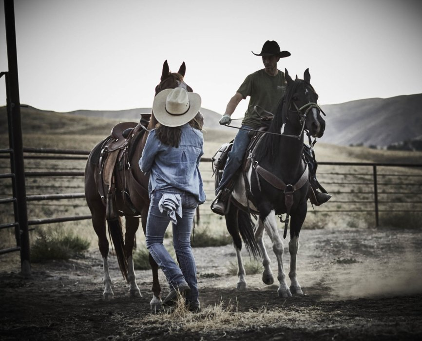 Two rancher wrangling up some horses and saddles
