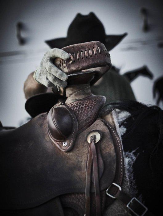 A rancher adjusting his saddle