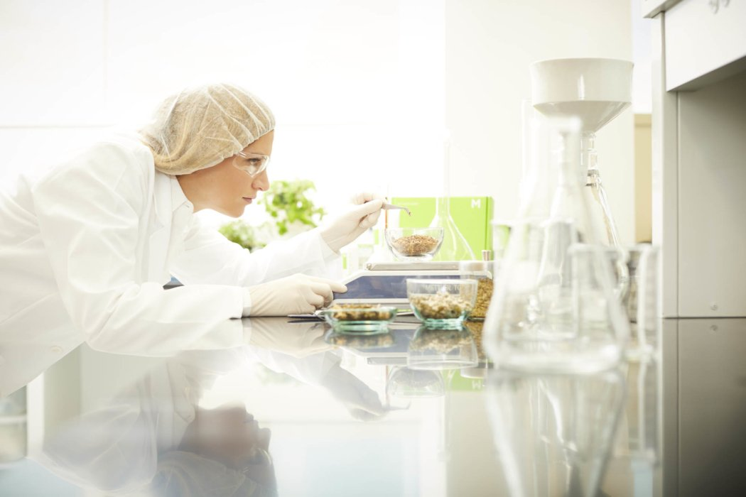 A female lab worker measuring mixtures on a scale