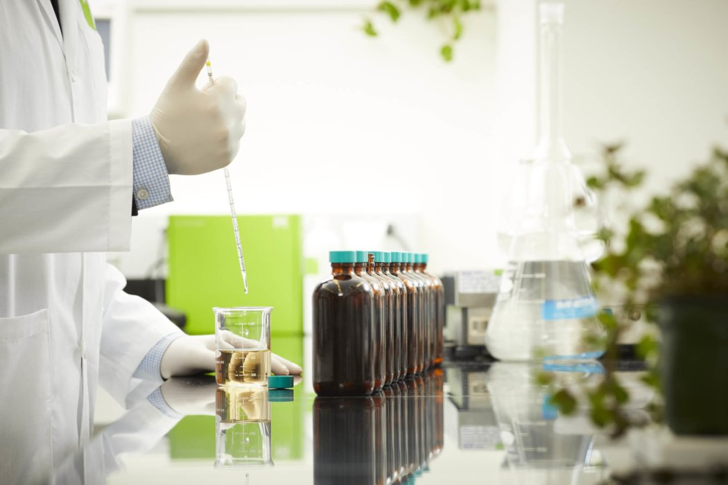 a lab worker with light amber liquid and pipette - Cosmetics photography