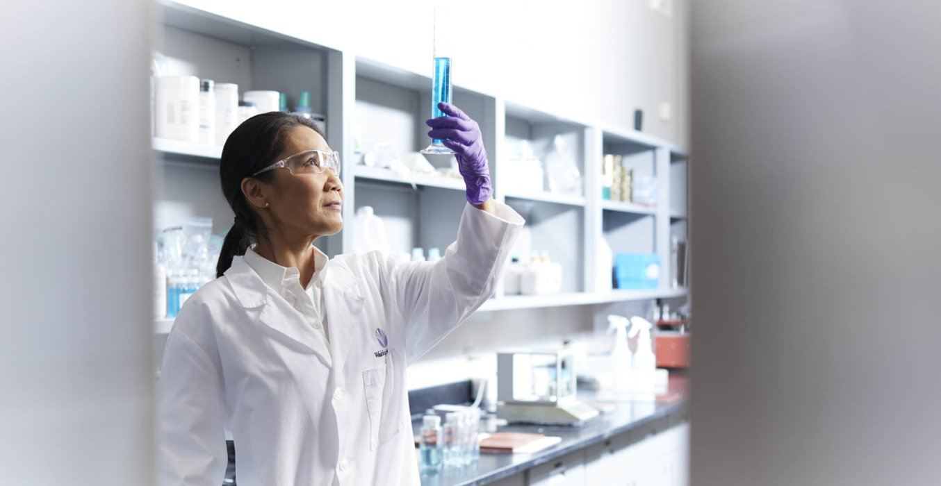 A female lab worker holding up a blue liquid filled test tube