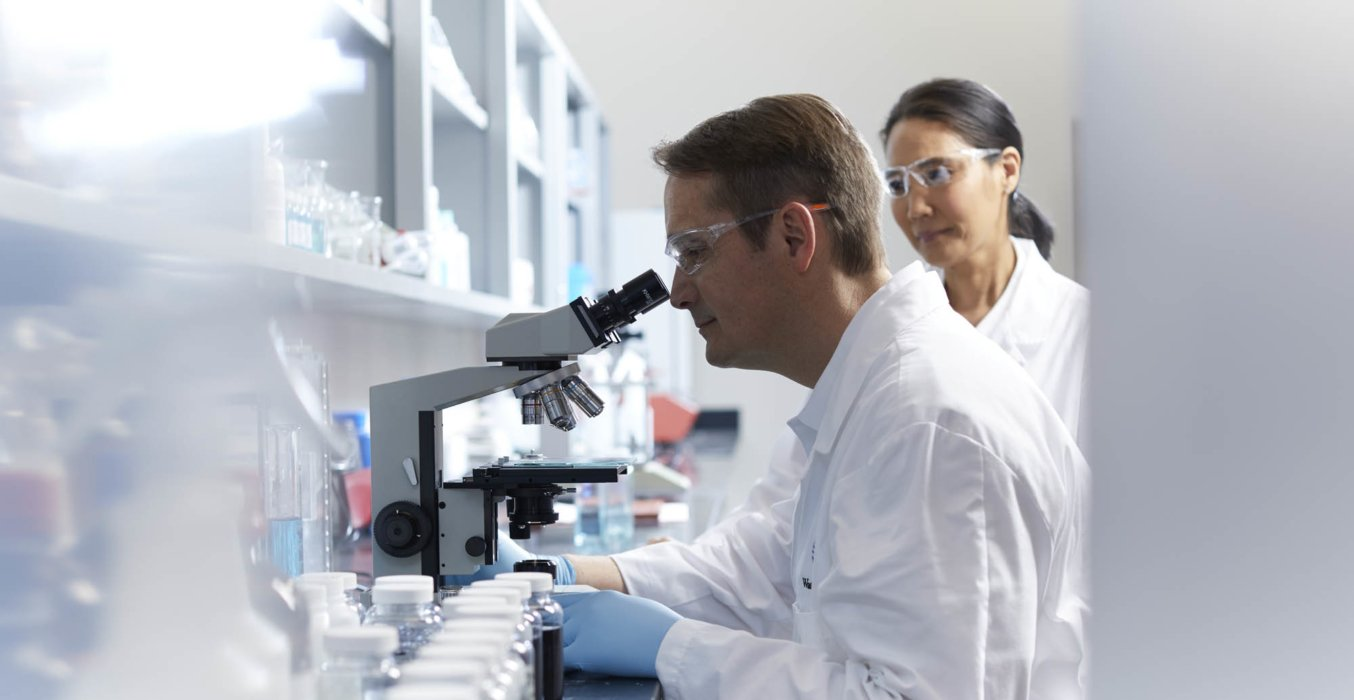 A male lab worker at a microscope