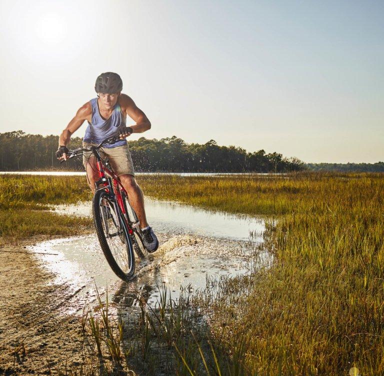 A young athletic man riding a bike through a wetland